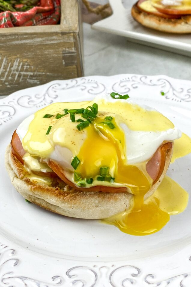 This Eggs Benedict recipe features buttery English muffins, back bacon, & poached eggs, all smothered in an easy blender hollandaise sauce.