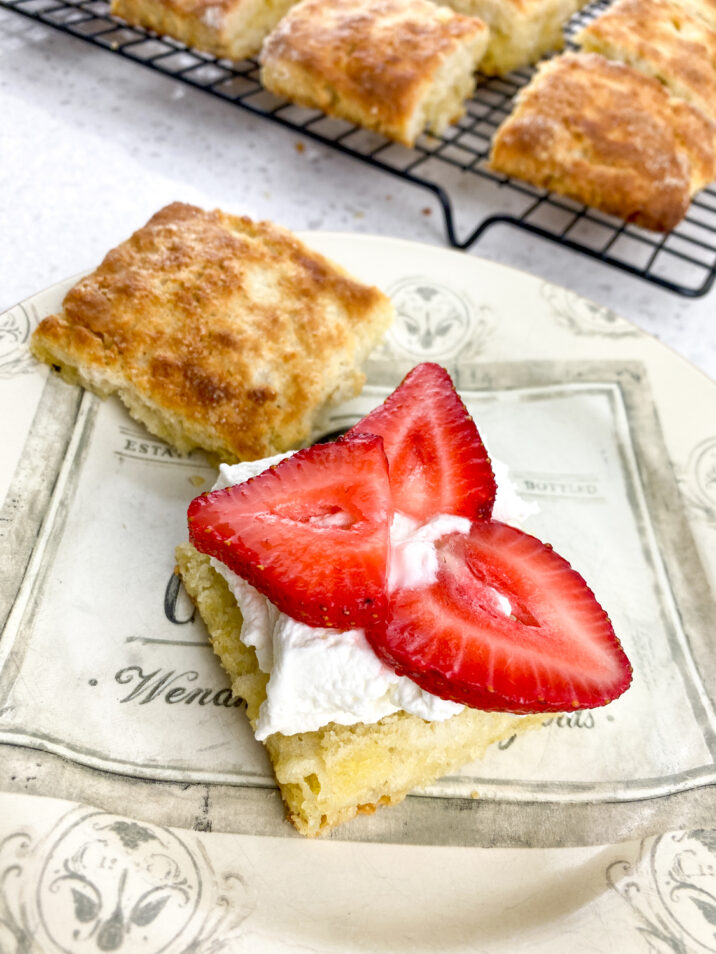 shortcakes sliced in half and topped with whipped cream and strawberries.